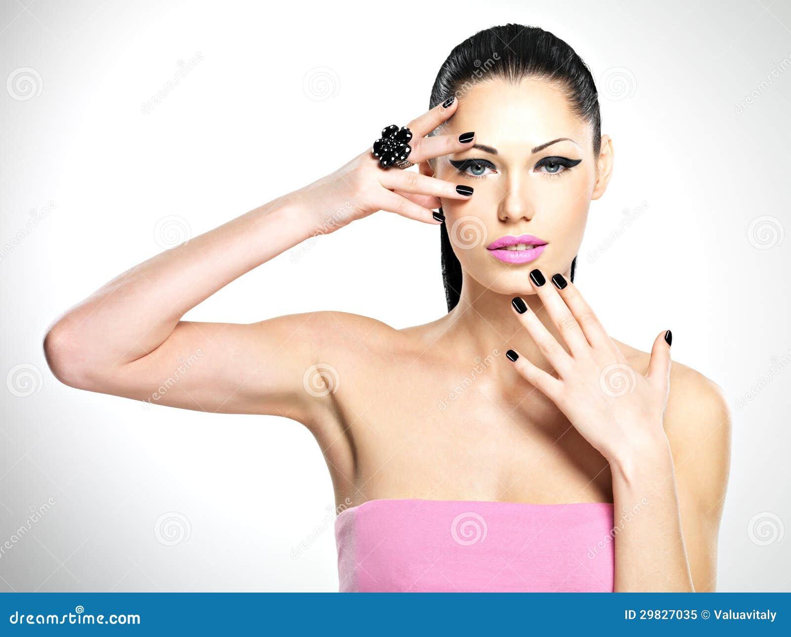 Cara da mulher bonita com pregos pretos e os bordos cor-de-rosa