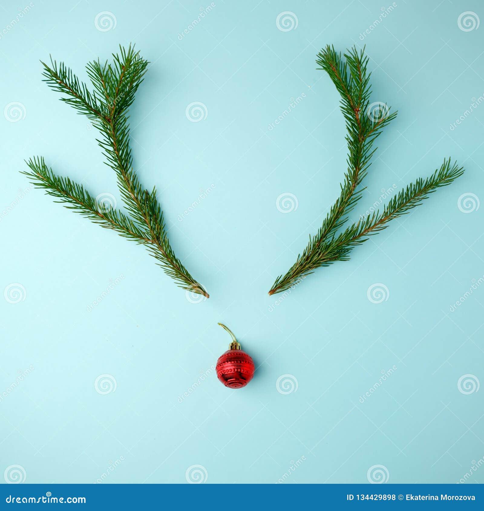 Cara da rena feita de ramos da decoração e do pinho do Natal no fundo azul Conceito mínimo do Natal Configuração lisa, vista supe