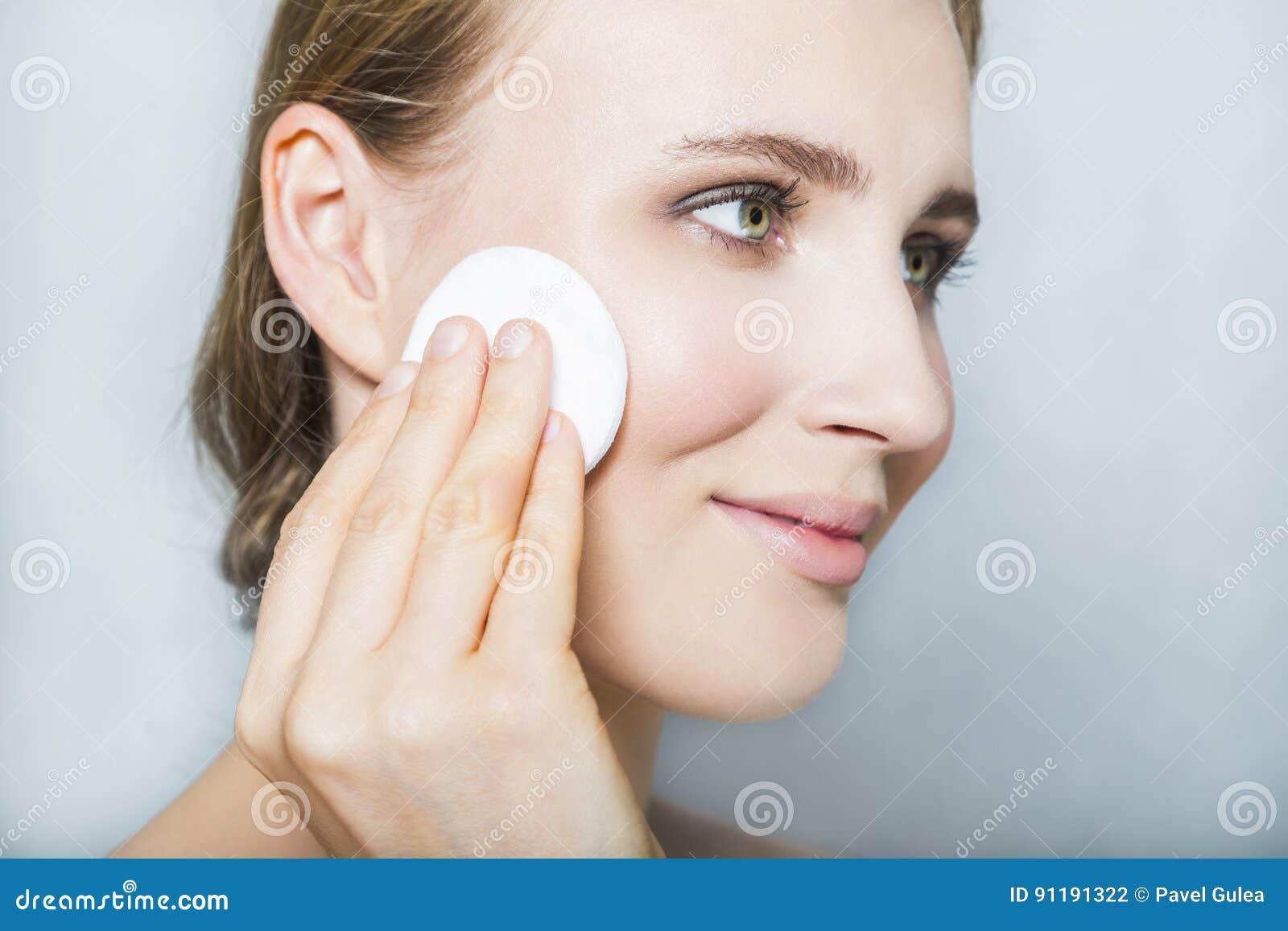 Cara de la muchacha hermosa rubia joven con maquillaje y el cojín de algodón