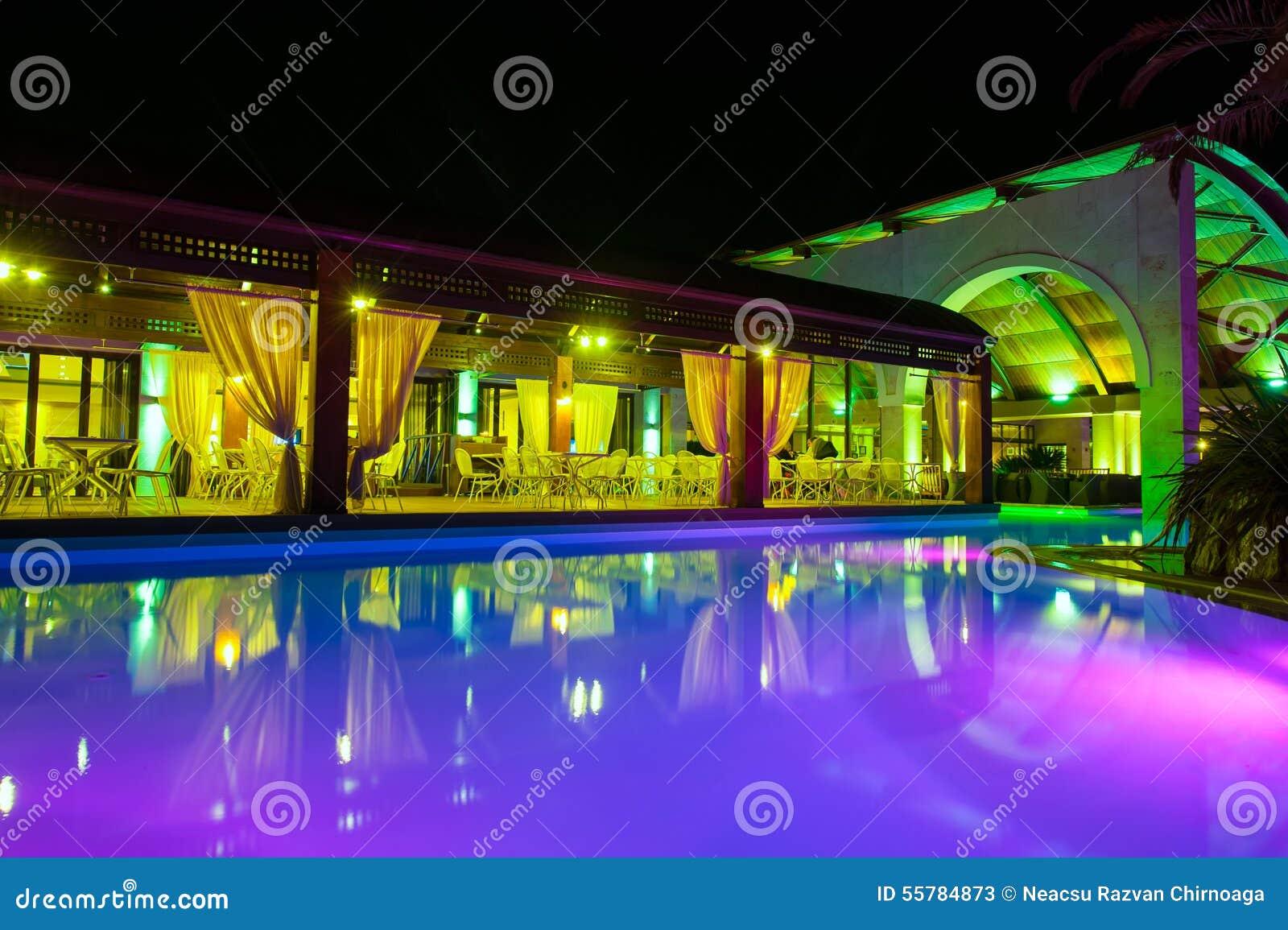 Cara de la piscina de la noche del hotel rico