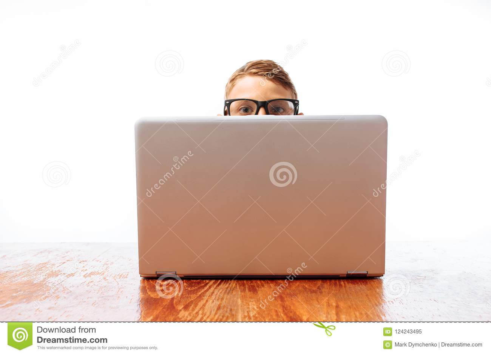 A cara de um homem novo olha para fora de debaixo do portátil, um adolescente que esconde atrás de um portátil no estúdio em um f