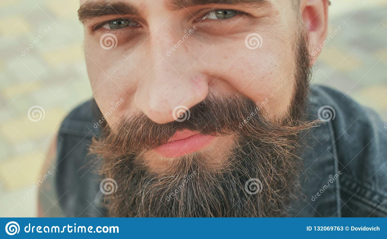 Cara del primer de un hombre de la calle barbudo, brutal y sonriente