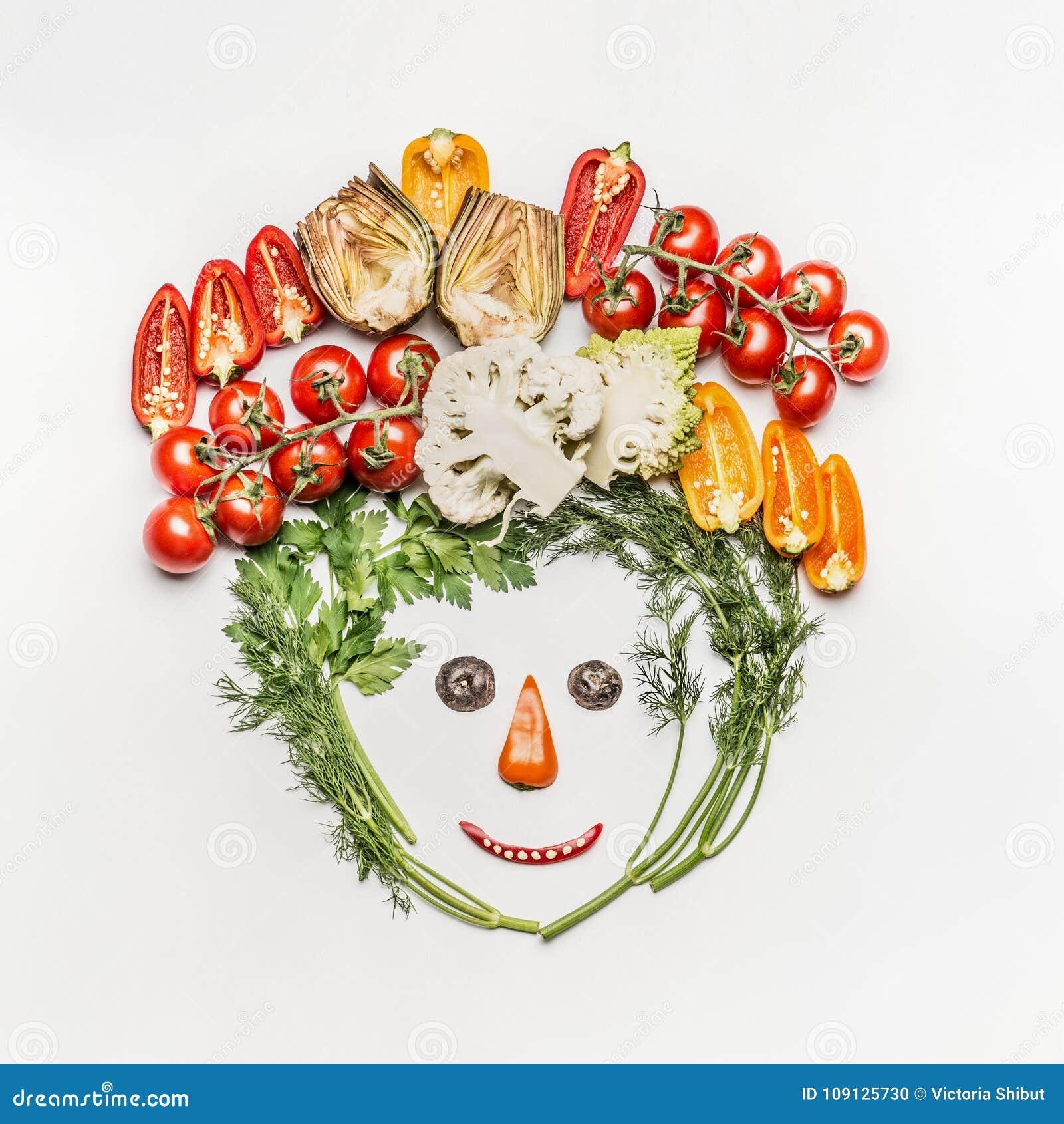 Cara divertida hecha de diversas verduras frescas en el fondo blanco, visión superior
