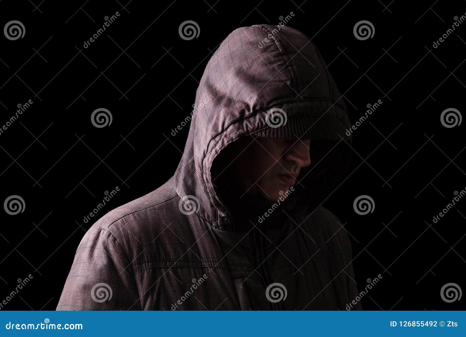 Cara escondendo só, deprimida e frágil do homem caucasiano ou branco, estando na escuridão