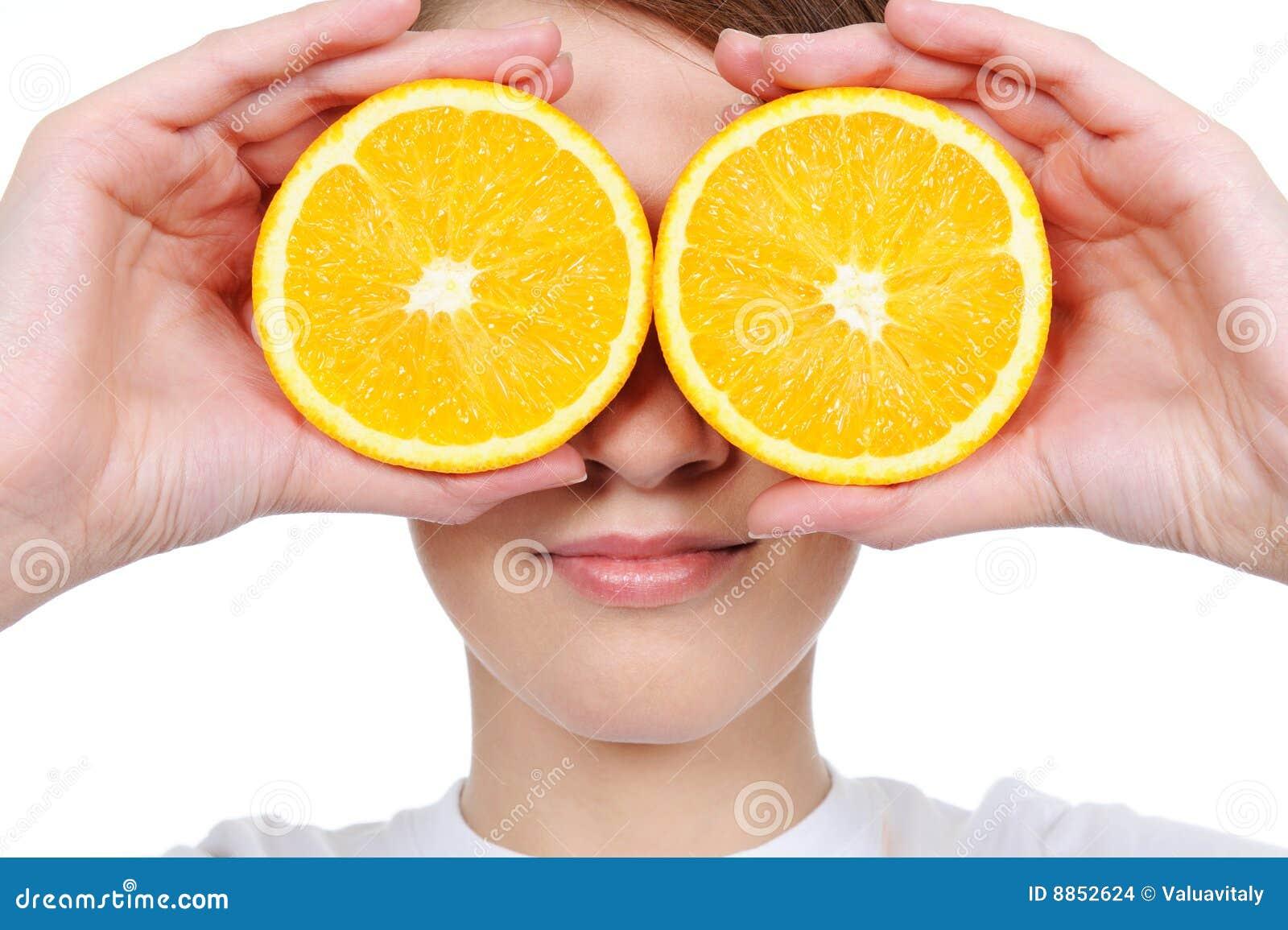 Cara femenina con la naranja fresca de la sección