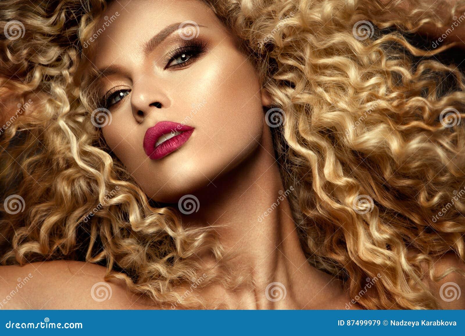 Cara hermosa de un modelo de moda con los ojos azules Pelo rizado Labios rojos