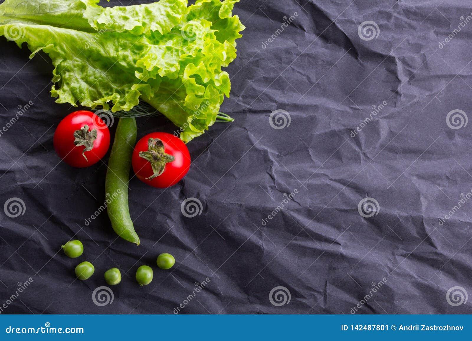 Cara sonriente de verduras en fondo de papel negro Con el espacio para el texto