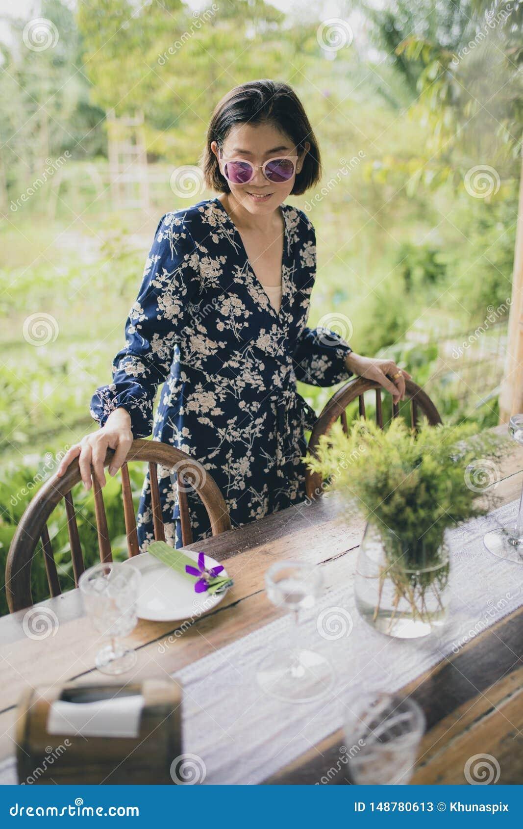 Cara sonriente dentuda de la mujer asiática hermosa con la emoción de relajación al lado de la tabla de la comida