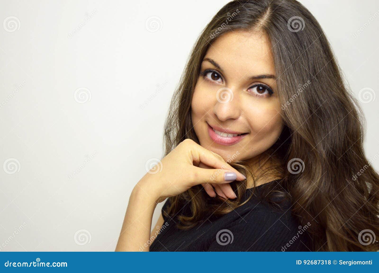 Cara sonriente, feliz, positiva, despreocupada de la mujer joven que mira la cámara con el espacio en blanco al tiro del lado, pr