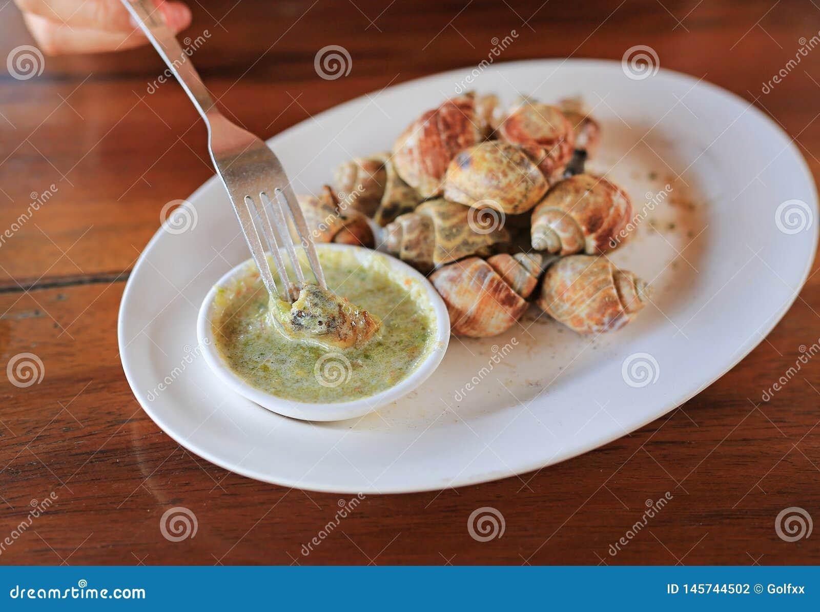 Caracol grelhado delicioso de babylon da espiral com molho de pimentão na forquilha pronto para comer O marisco tailand?s famoso