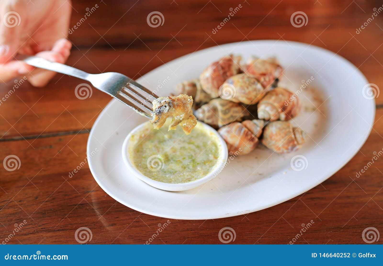 Caracol grelhado delicioso de babylon da espiral com molho de piment?o na forquilha pronto para comer O marisco tailand?s famoso