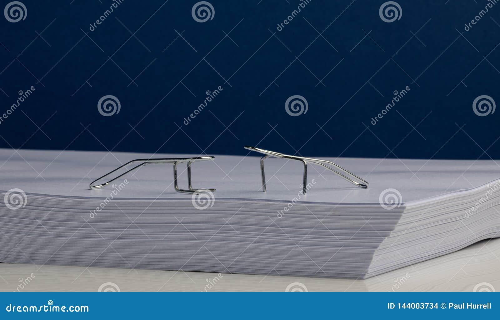 Caracteres del clip de papel que hacen ejercicios en la resma de papel
