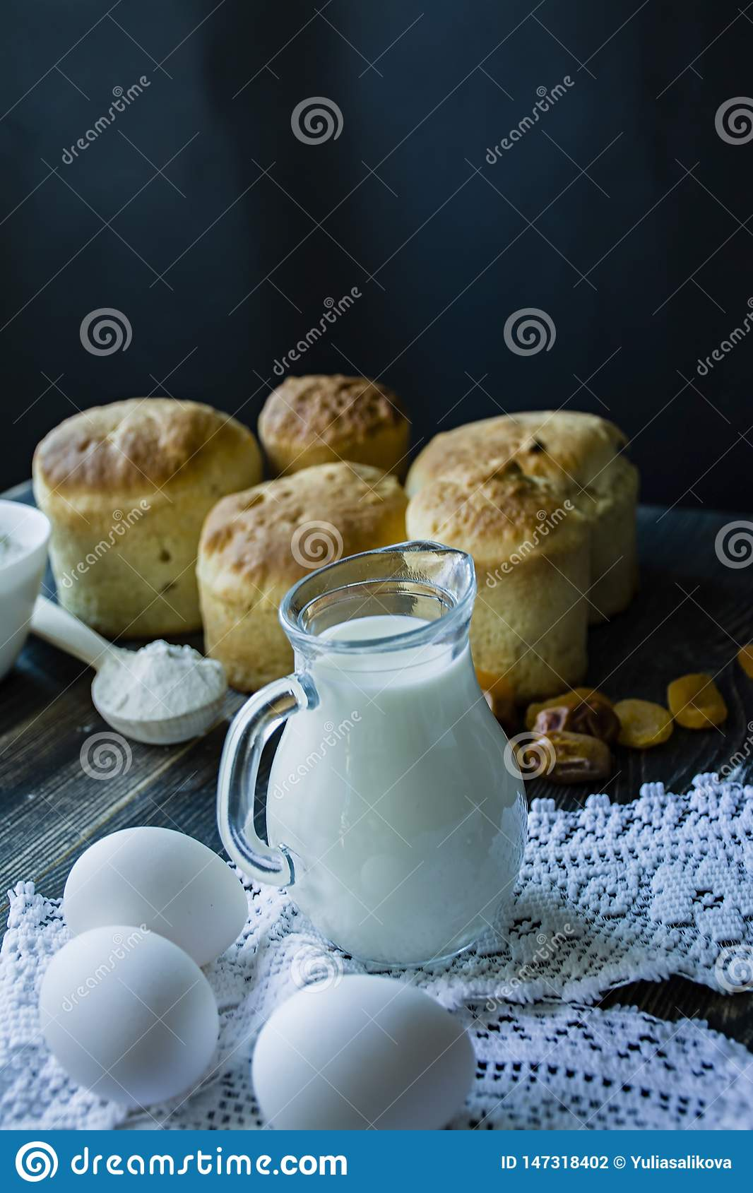 Carafe with milk in the background Easter cakes on a dark background. Fresh cakes with dried fruits. The process of cooking Easter