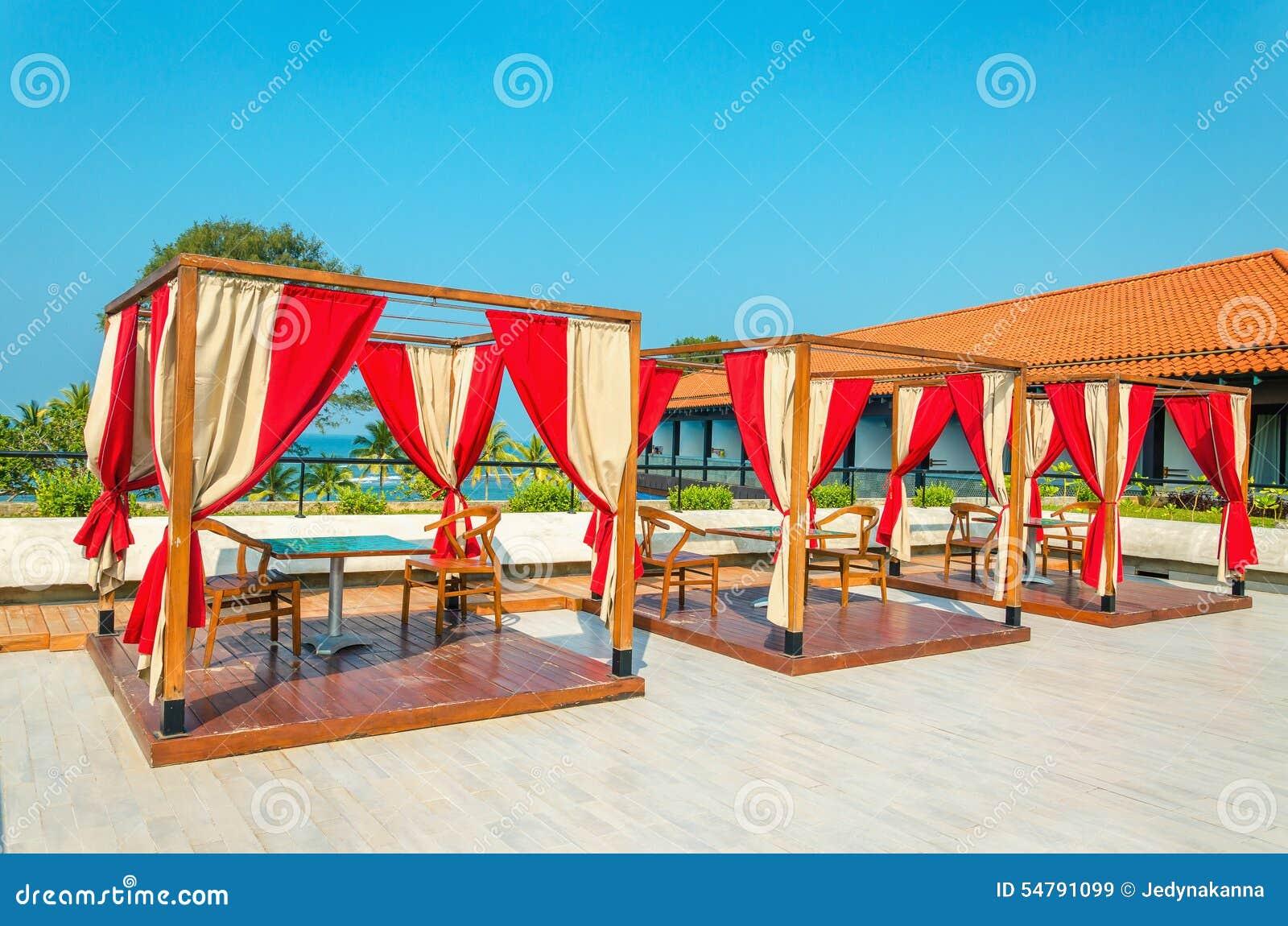 Caramanchões com tabelas e cadeiras no restaurante