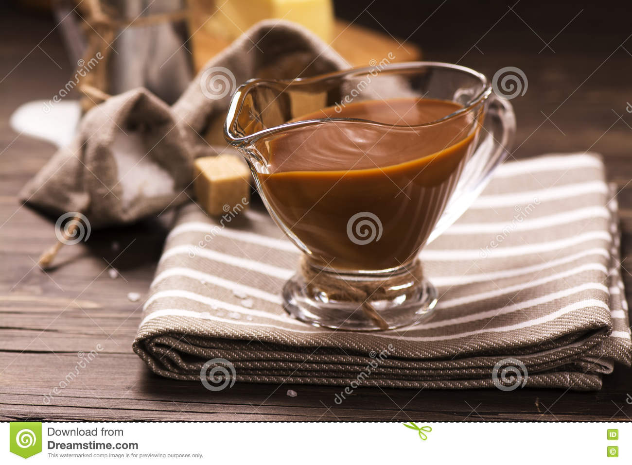 Caramel sauce and ingredients over grunge wooden background.