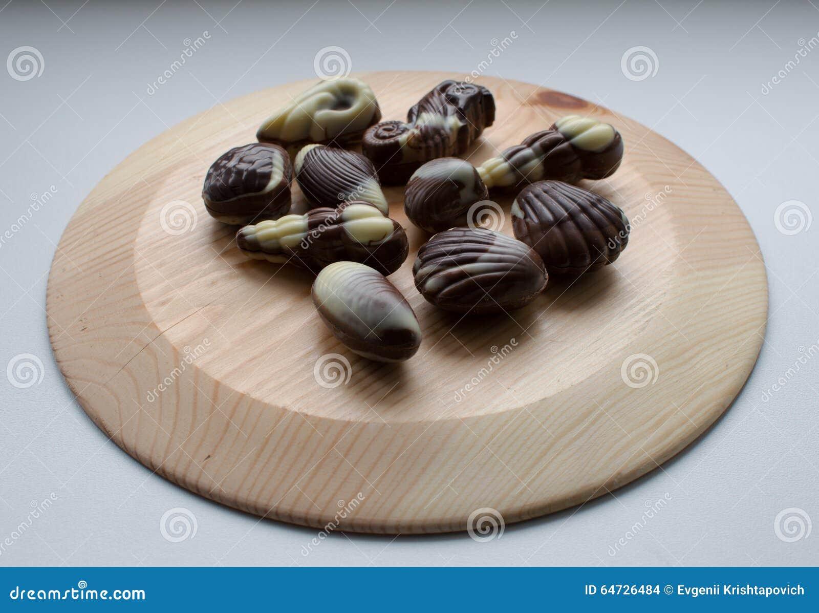 Caramelle di cioccolato sul piatto di legno