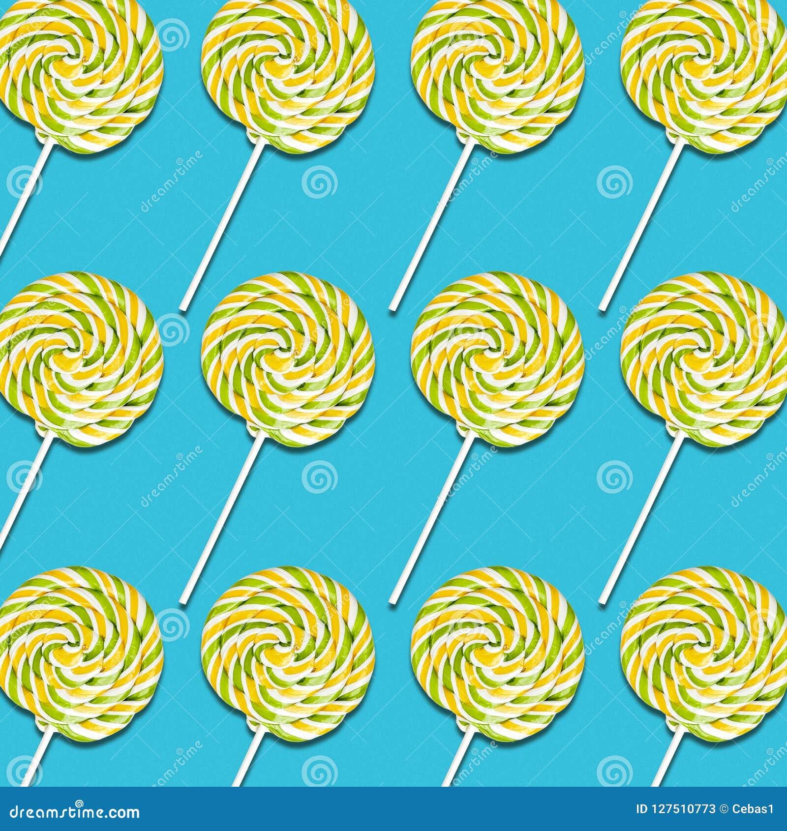 Caramelle gialle e verdi della lecca-lecca sul fondo del turchese