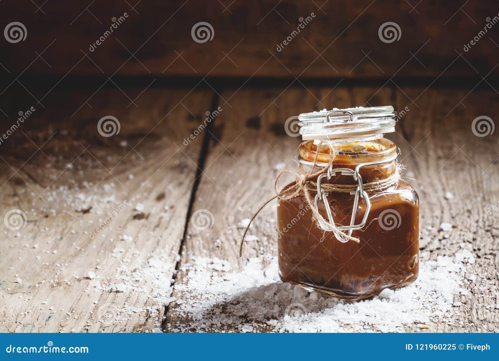 Caramello salato casalingo in un barattolo di vetro con un coperchio, sal spruzzato