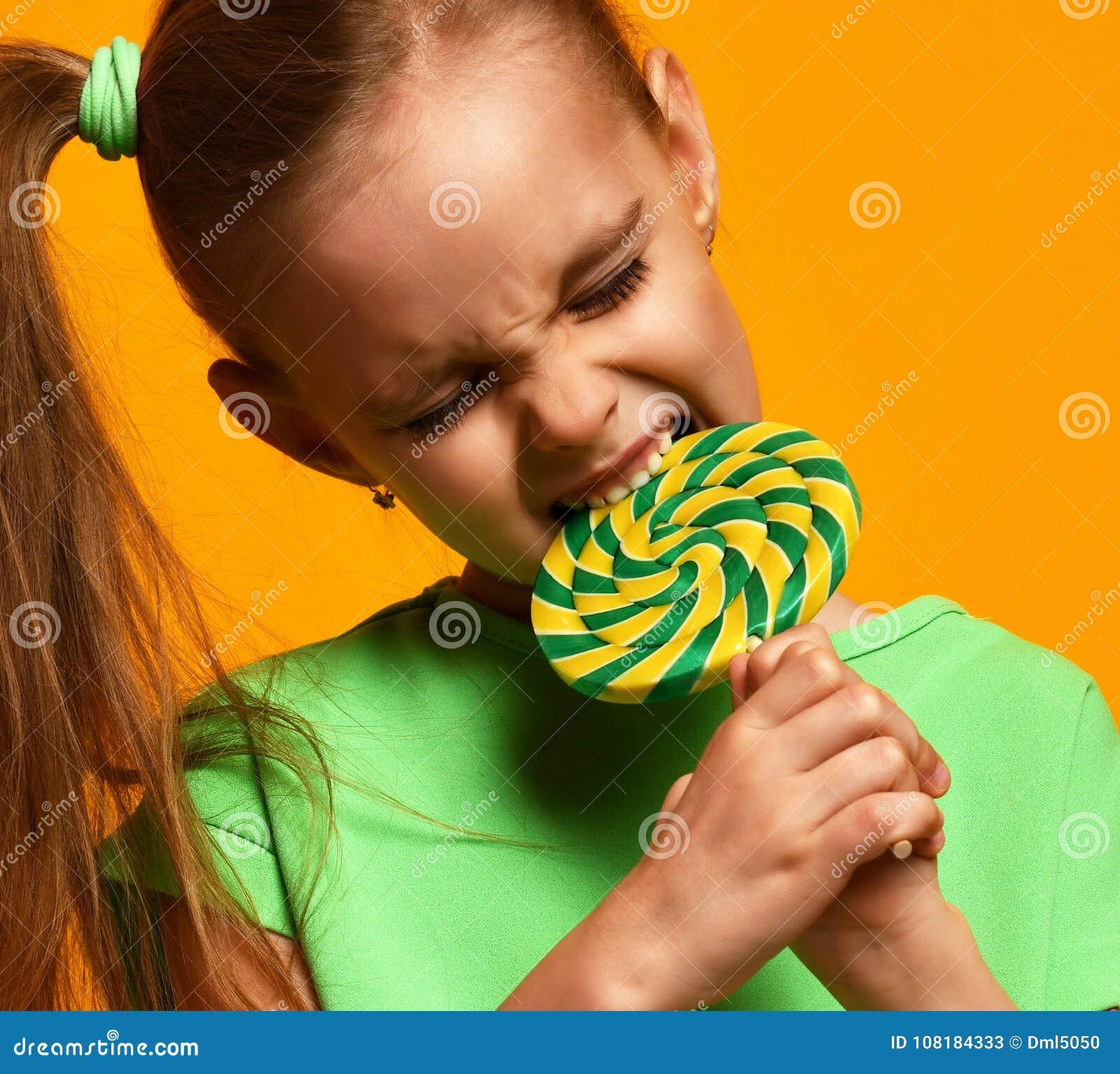 Caramelo dulce del lollypop del pequeño niño de la muchacha de la mordedura joven feliz del niño