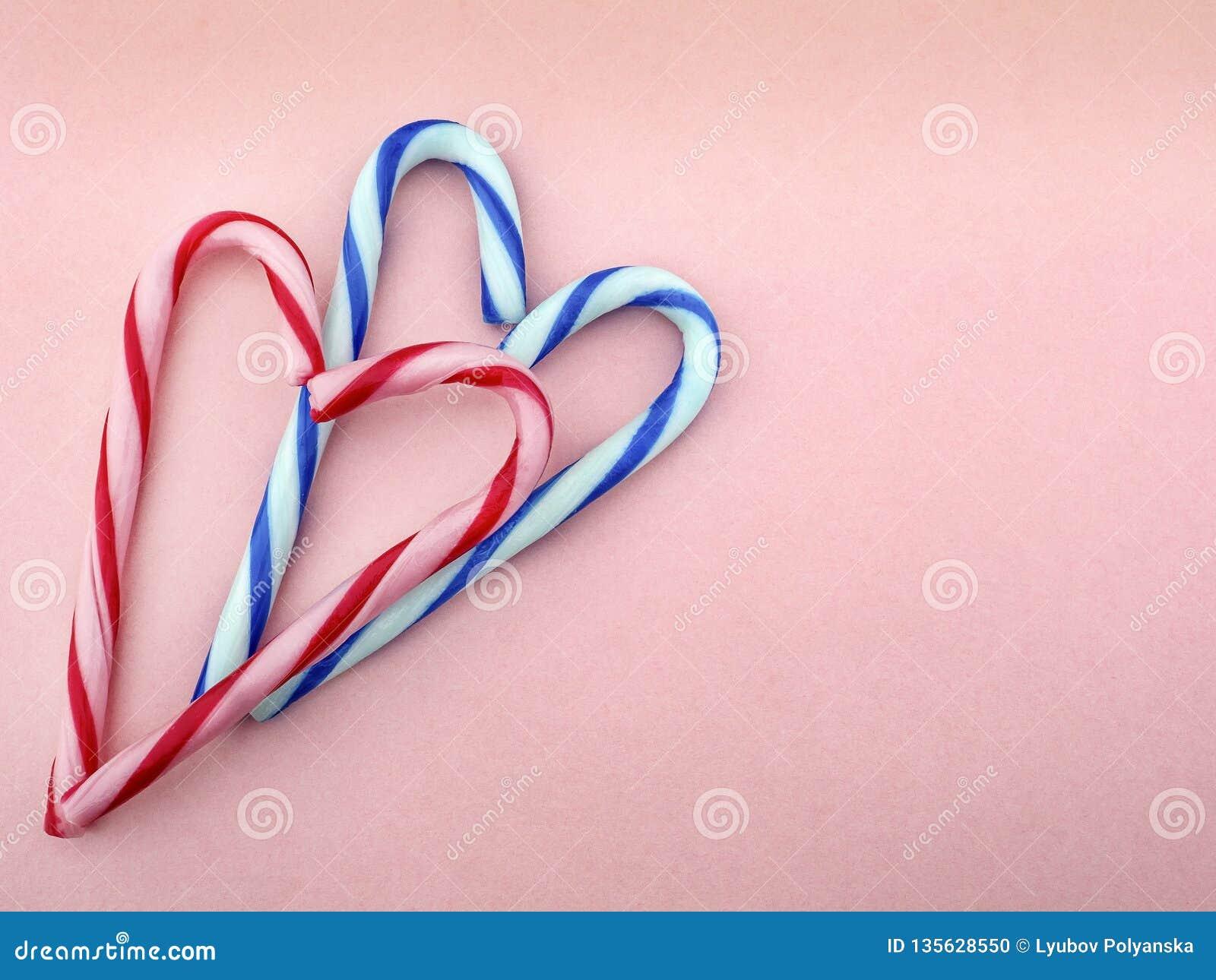 Caramelo en blanco y rosado y en las rayas blancas y azules dobladas en la forma de corazones en un fondo rosado