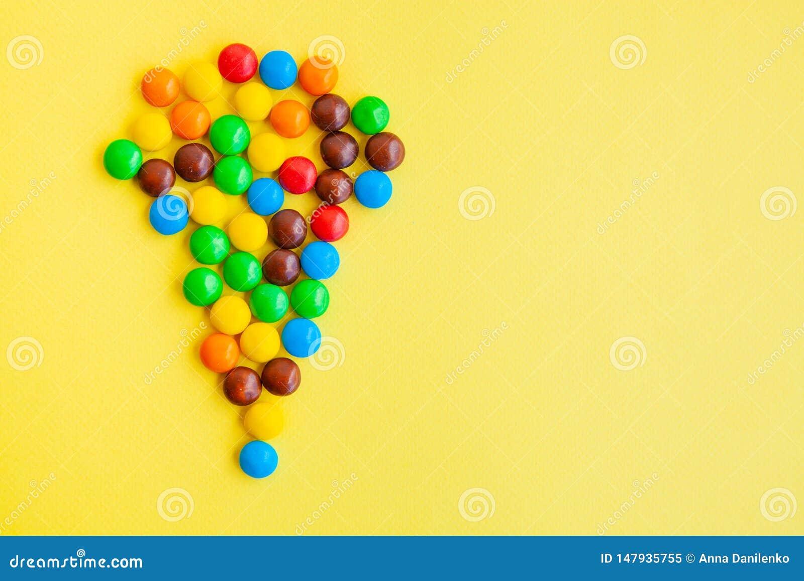 Caramelos coloridos en fondo amarillo