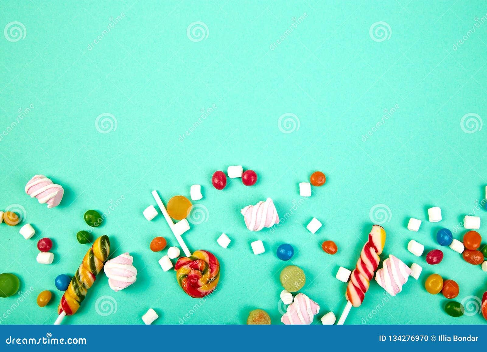 Caramelos coloridos en fondo en colores pastel de la turquesa Endecha plana