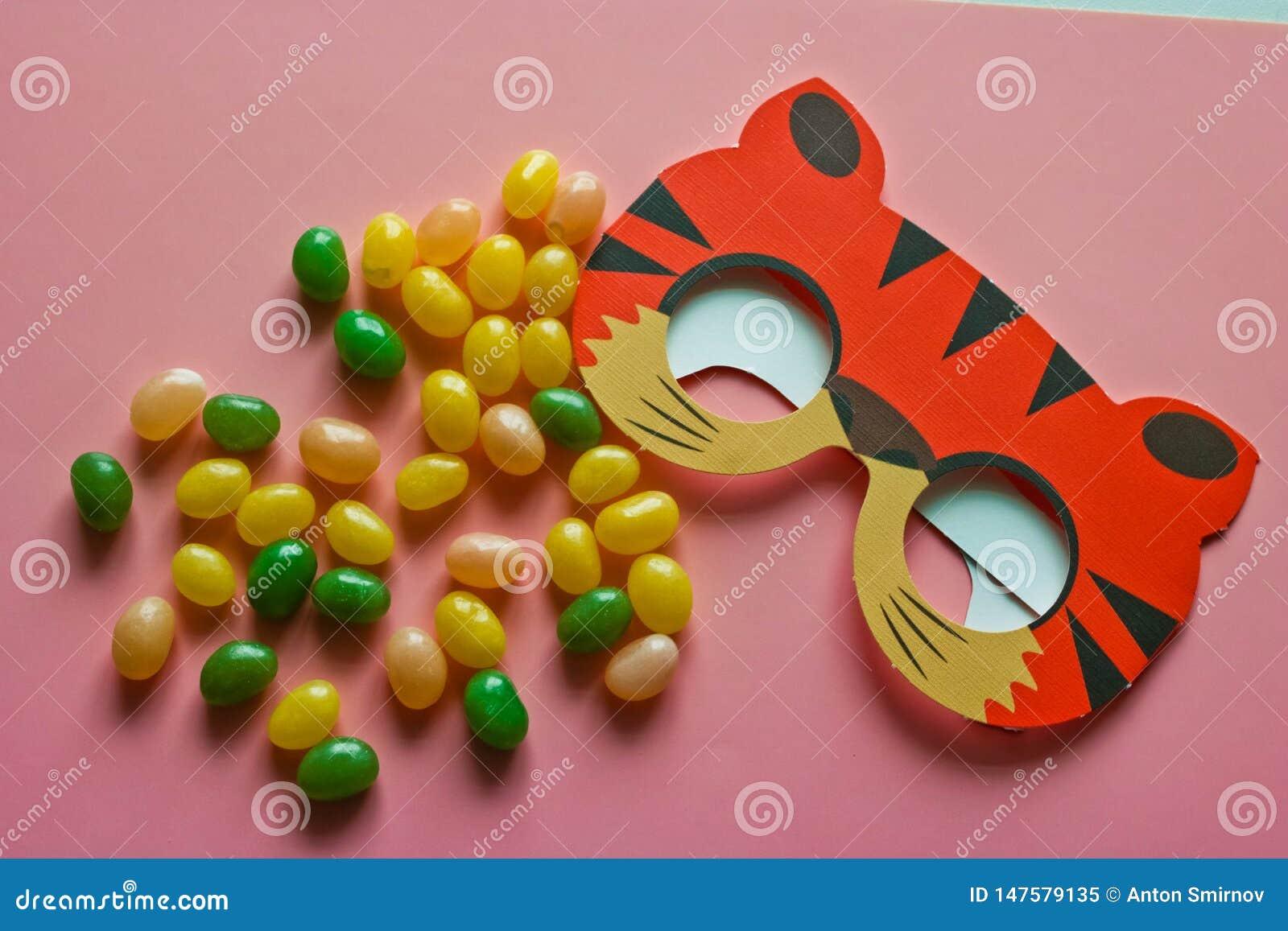 Caramelos dulces que dispersan en máscara rosada del carnaval del fondo y de los niños Concepto del d?a de fiesta