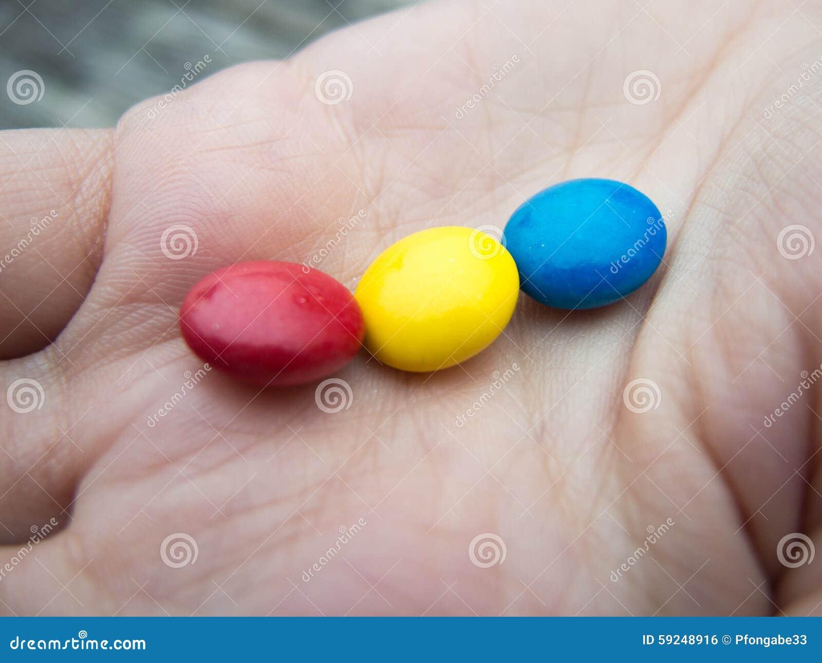 Caramelos tricolores en una mano