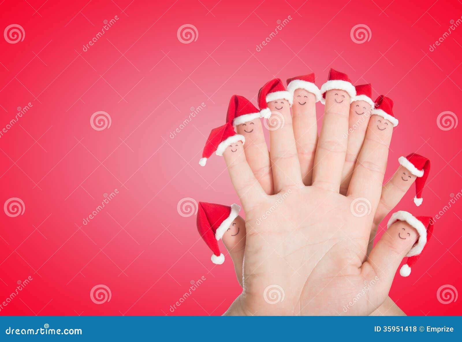 Caras de los fingeres en los sombreros de Papá Noel Familia feliz que celebra