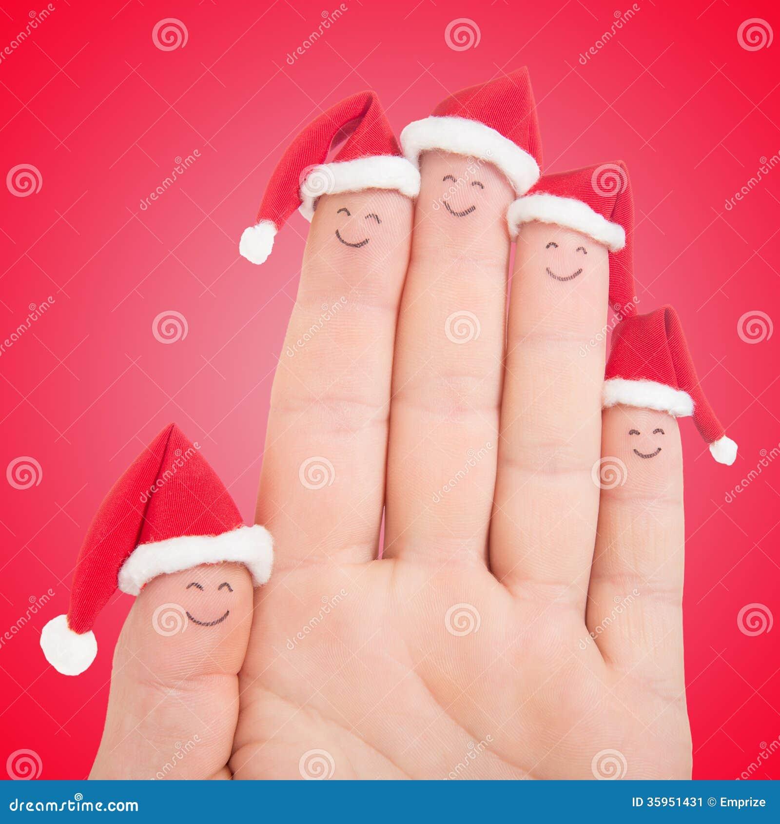Caras de los fingeres en los sombreros de Papá Noel Familia feliz que celebra concepto
