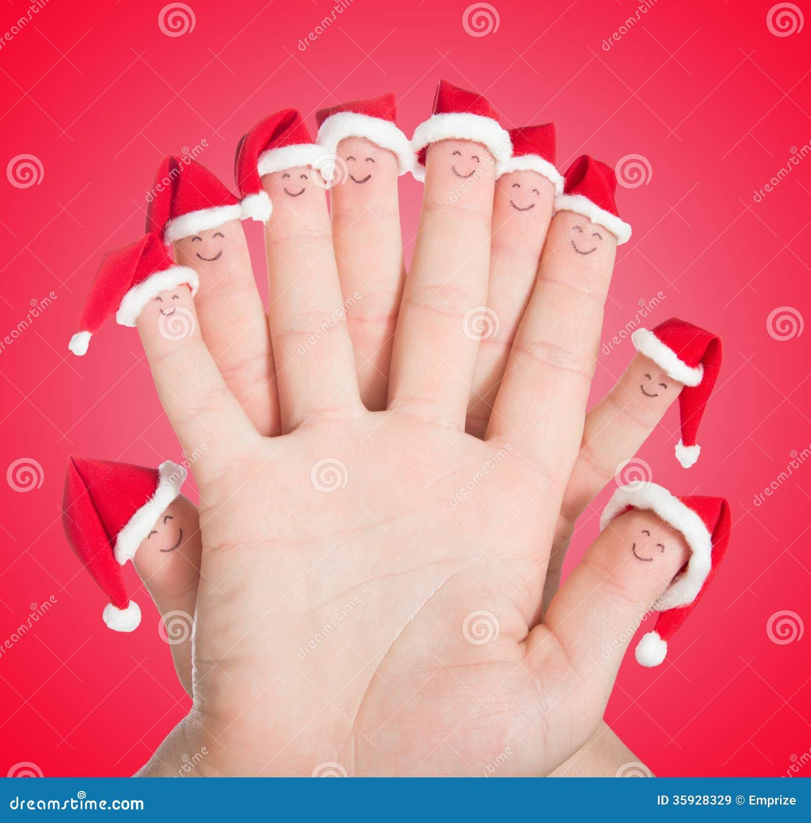Caras de los fingeres en los sombreros de Papá Noel Familia feliz que celebra el concepto FO