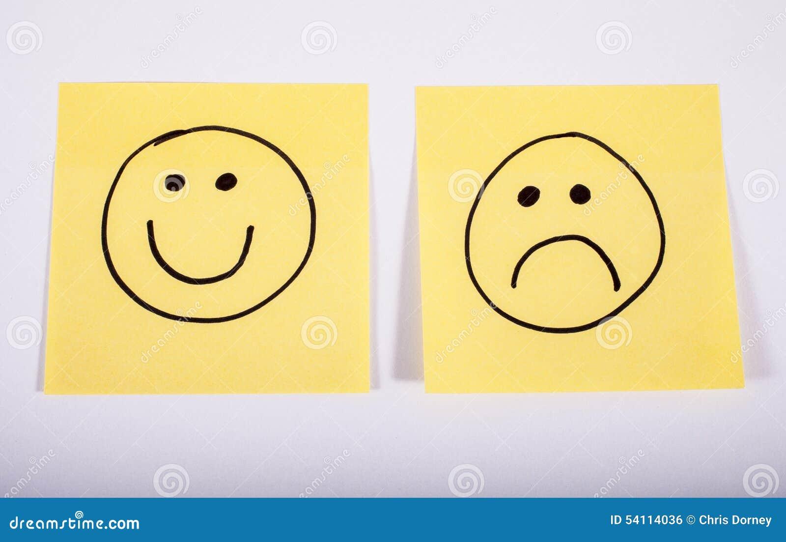 Caras Felices Y Tristes En El Papel De La Nota Foto De