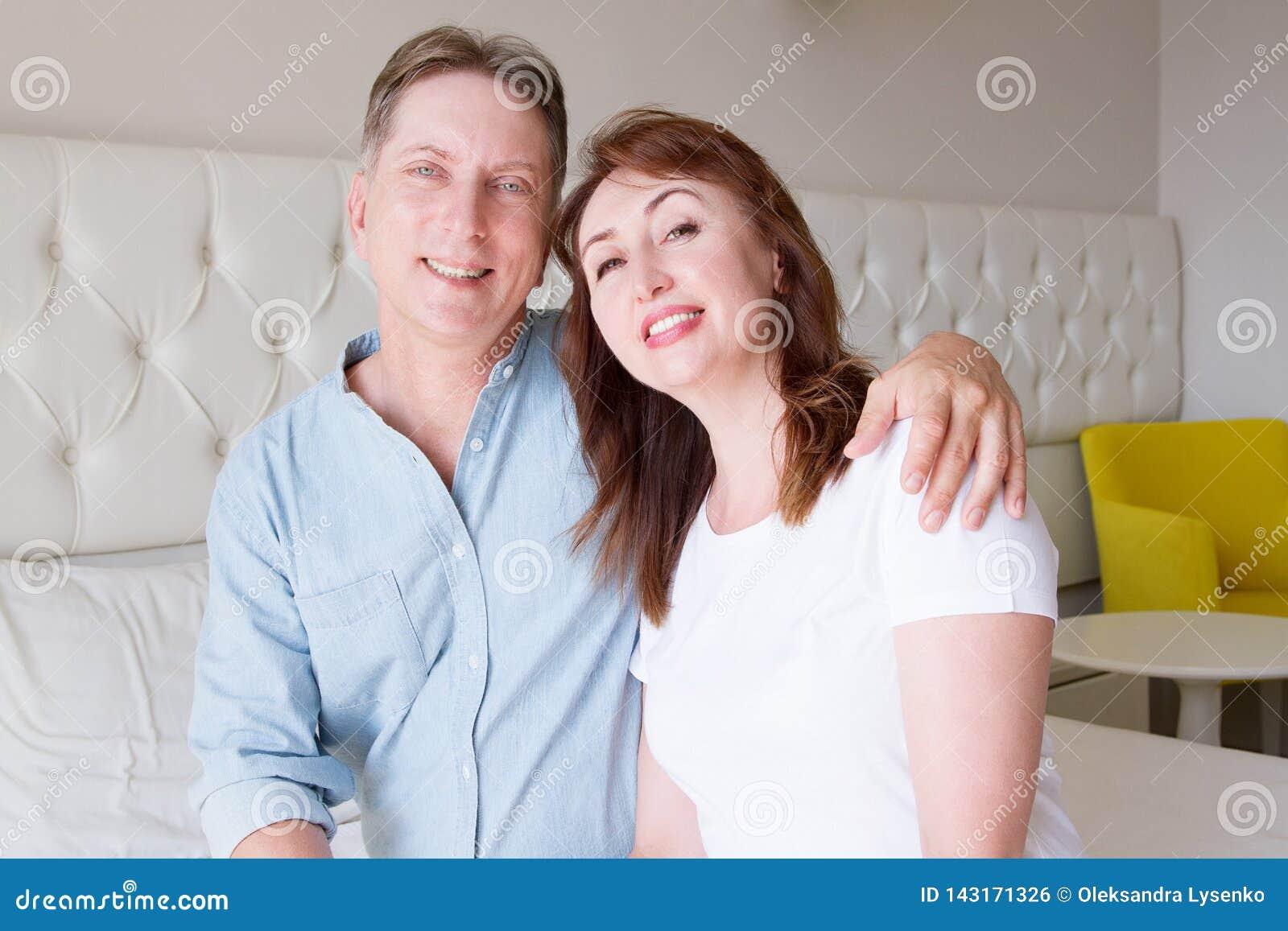 Caras felizes dos povos do close up Pares de sorriso da Idade Média em casa Fim de semana do tempo do divertimento da família e r