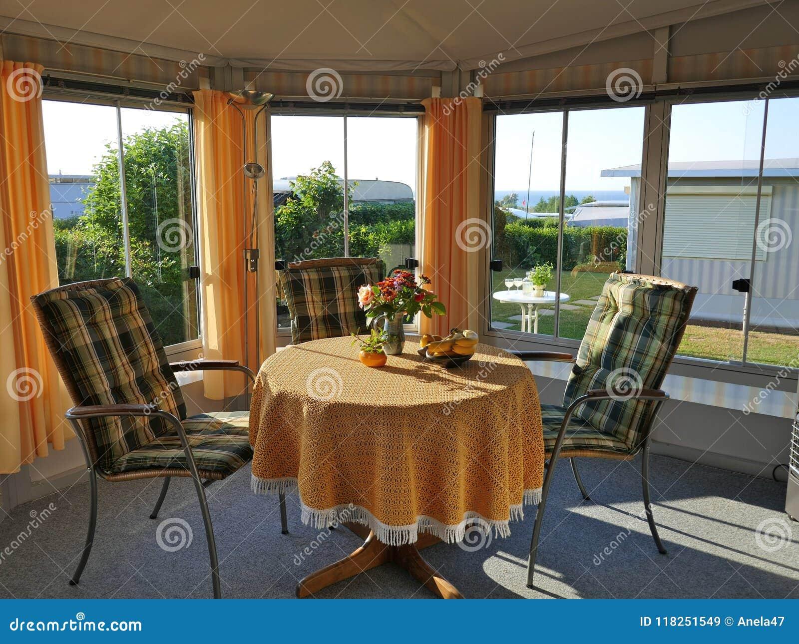Caravan con un portico fisso, fatto del tessuto della tenda, delle finestre di scivolamento di vetro e dei ciechi su un campeggio