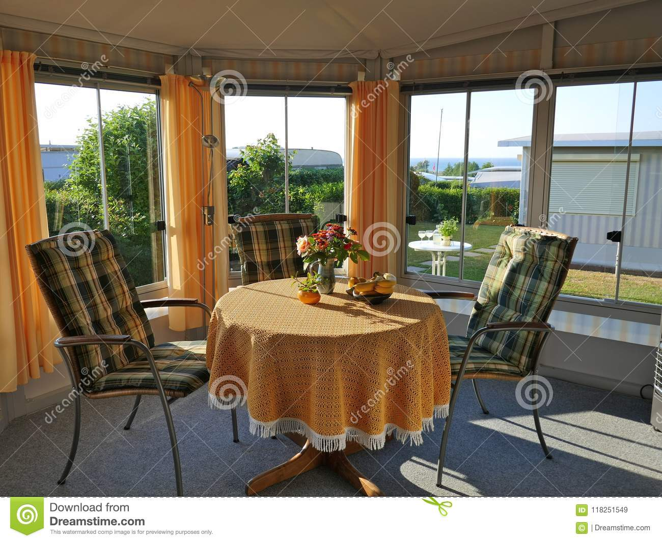 Caravan with a fixed porch, made of awning fabric, glass sliding windows and blinds on a German campsite.