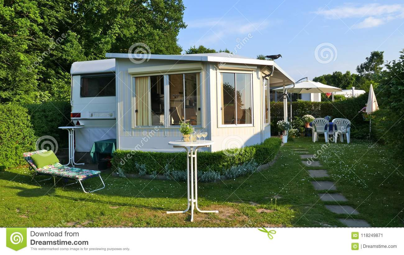 Caravan with a fixed veranda made of awning fabric, glass sliding windows and blinds on a German campsite.