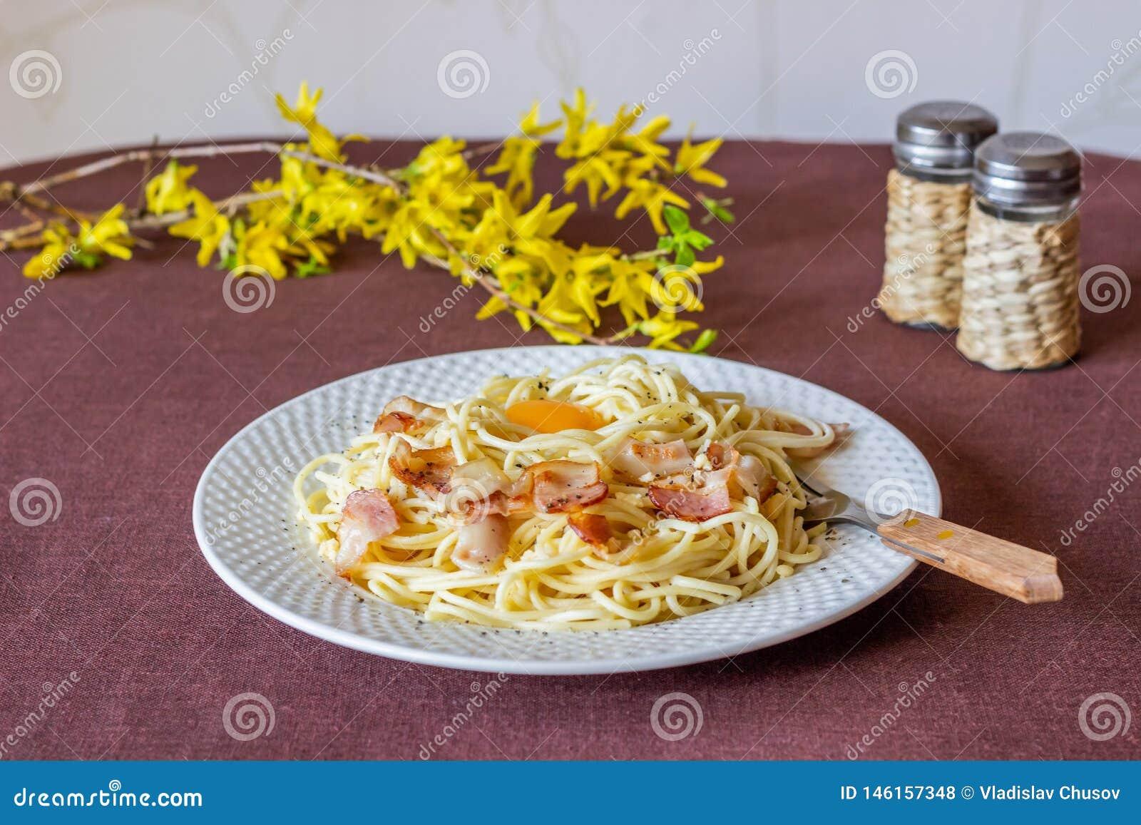 Carbonara de las pastas Flores en el fondo Alimento italiano