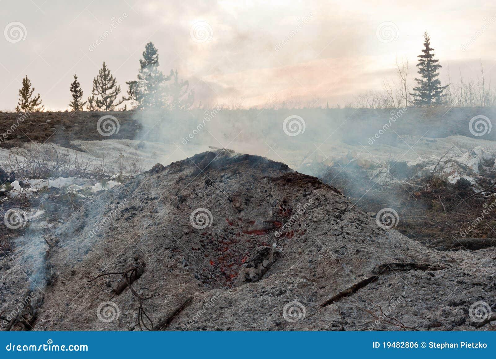 Carbones y cenizas que brillan intensamente y que fuman