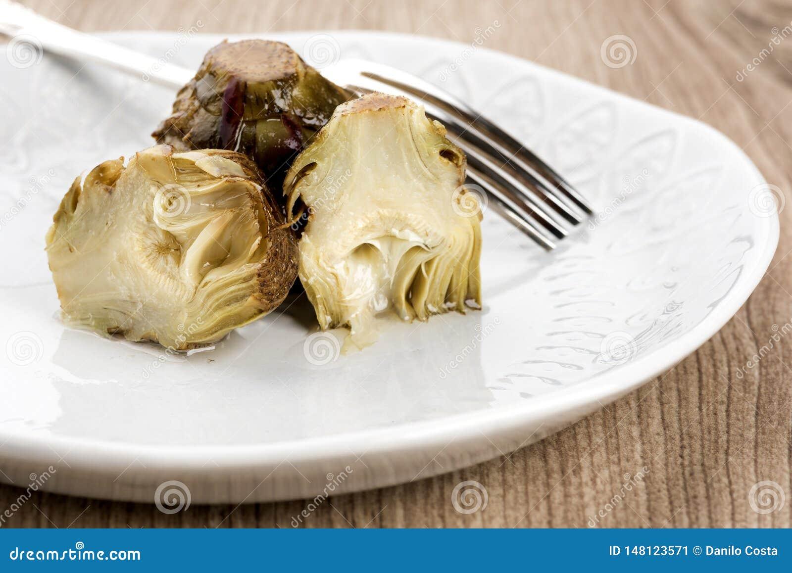 Carciofi in piatti o ciotola con la forcella