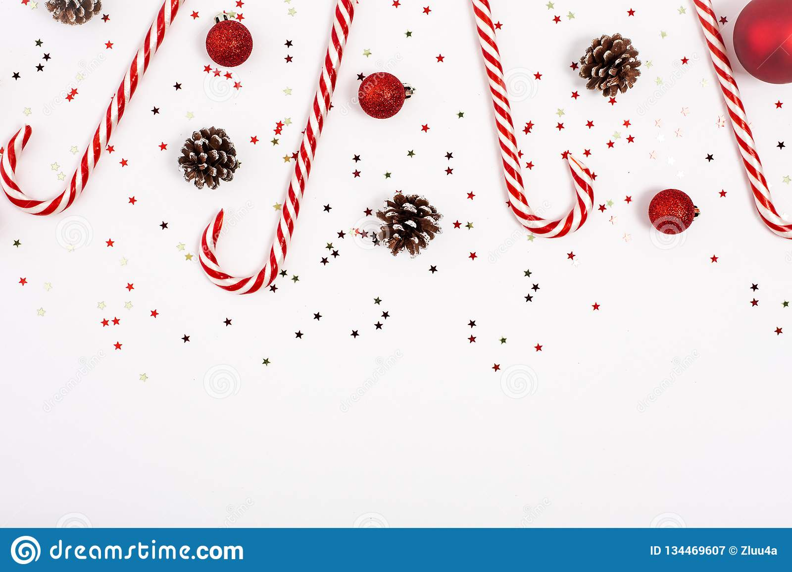 Christmas border made with candy cane, red balls and cones on white background. View from the top