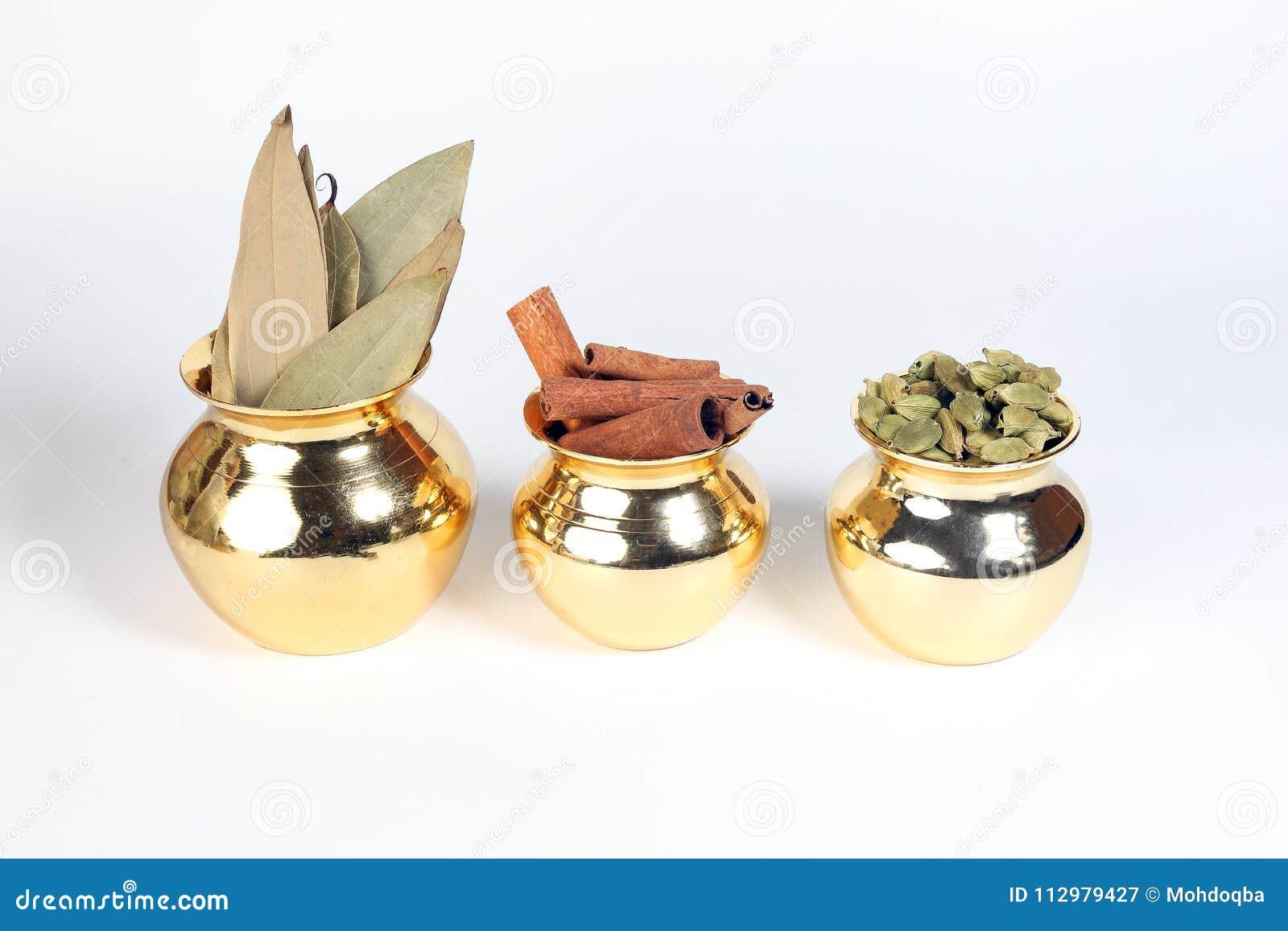 Cardamom cinnamon bay leaf spice in shiny metal pot