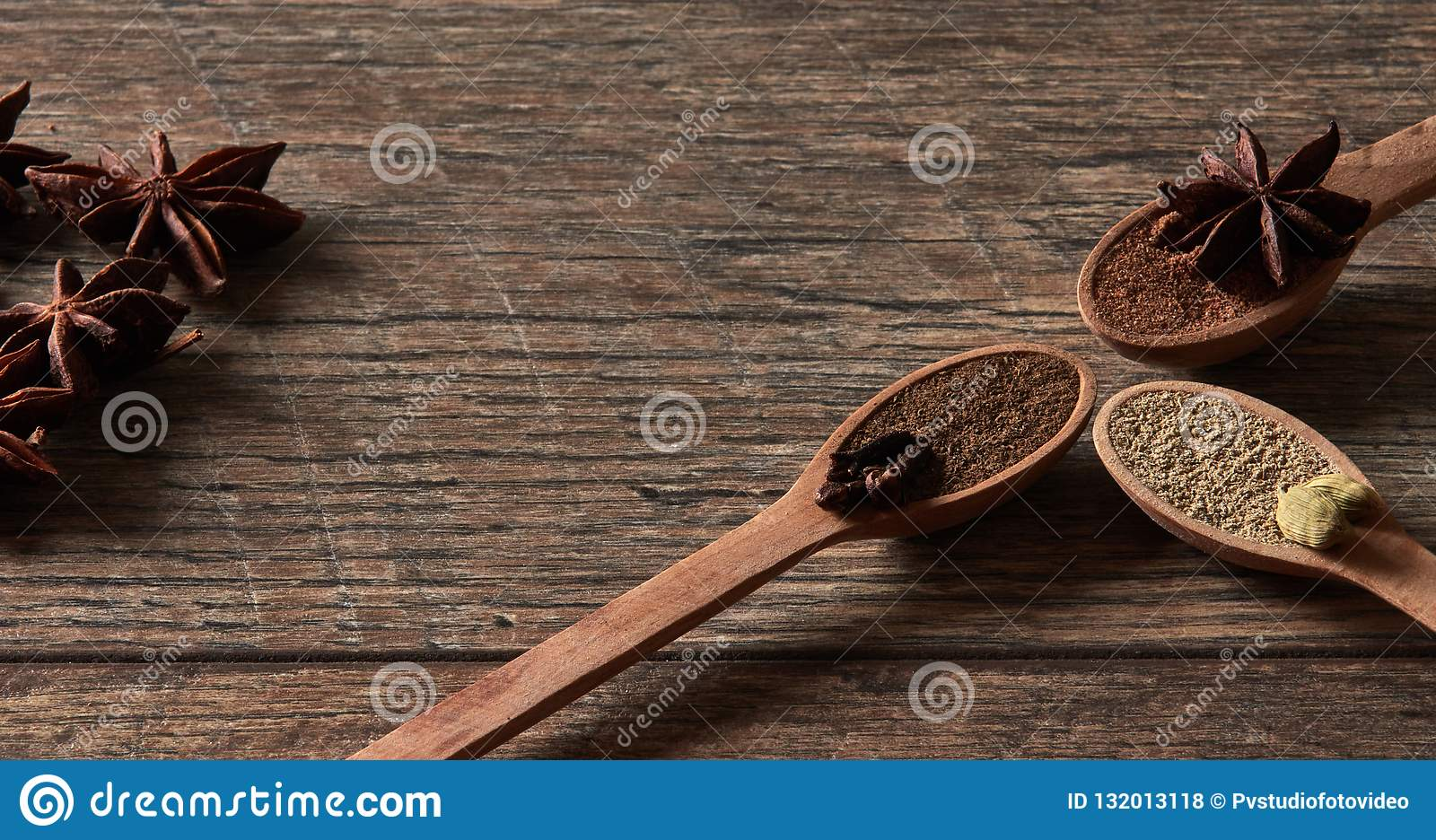 Cardamom, cloves, star anise. Ground spices in wooden spoons.Different types of whole Indian spices in wooden background
