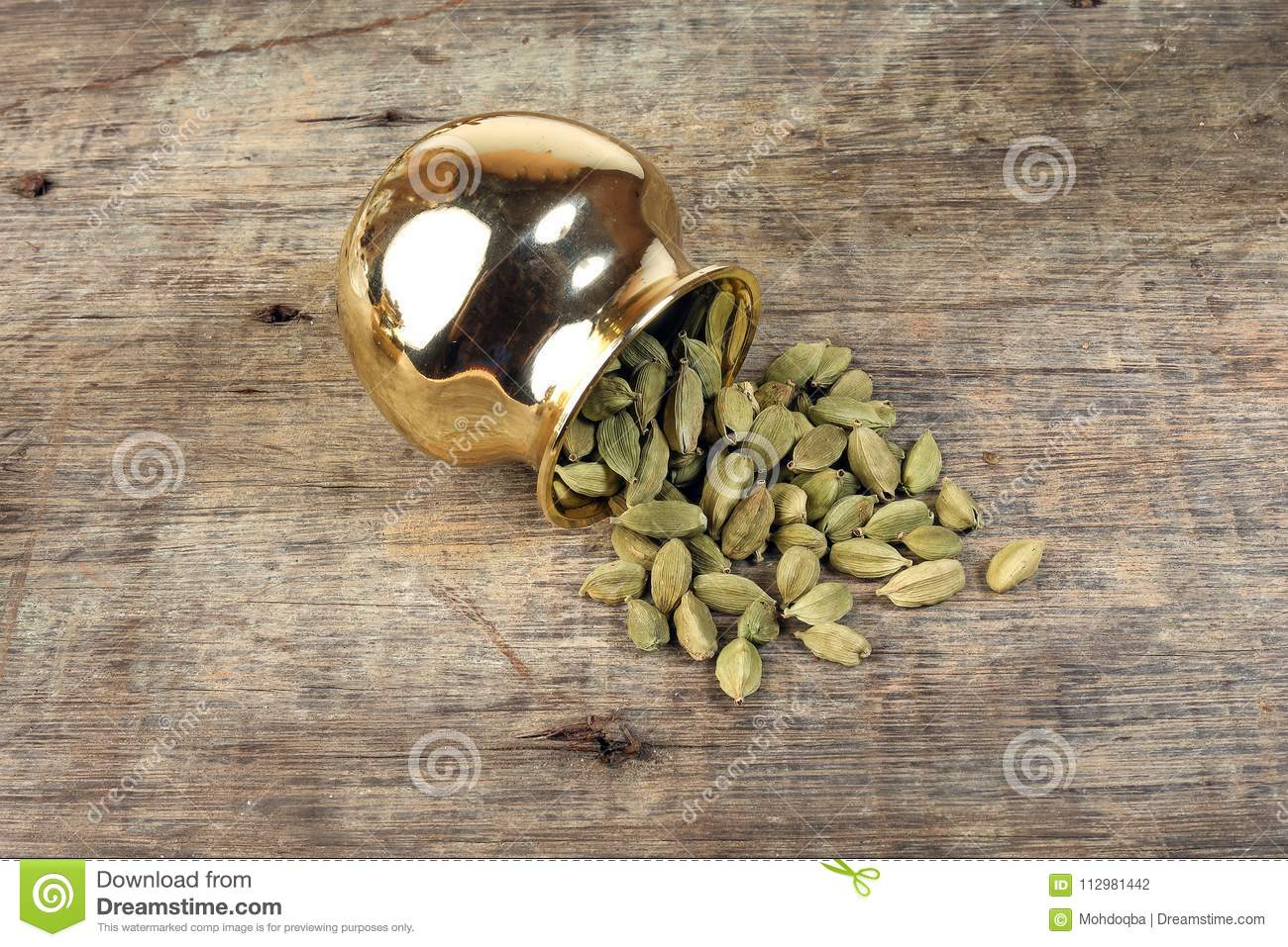 Cardamom spice in golden metal pot on rustic wood