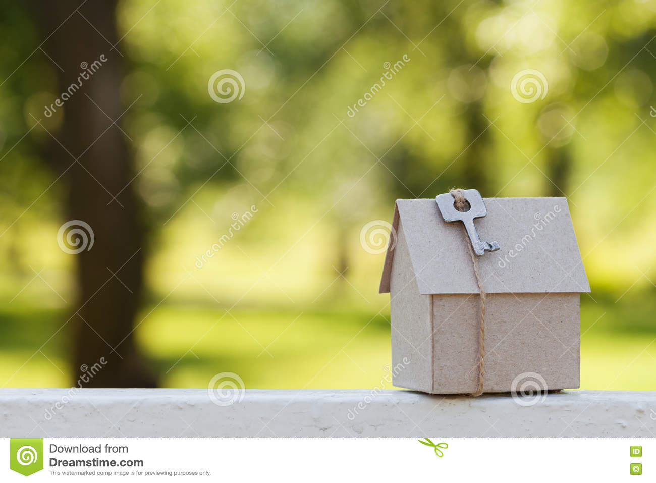 Cardboard house with key against green bokeh. Building, loan, housewarming, insurance, real estate or buying new home.