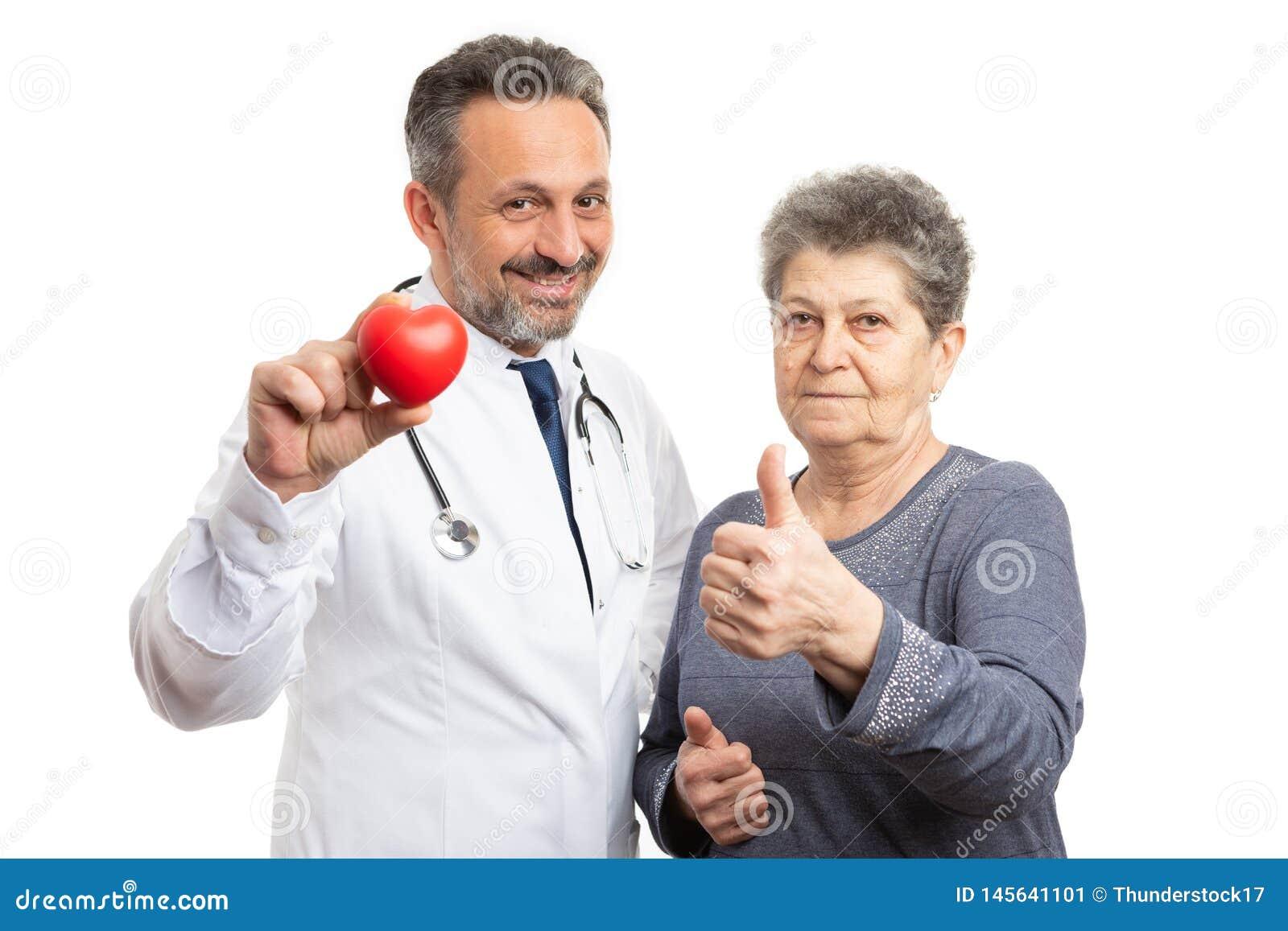 Cardiólogo que muestra el corazón y el pulgar de la tenencia del paciente para arriba