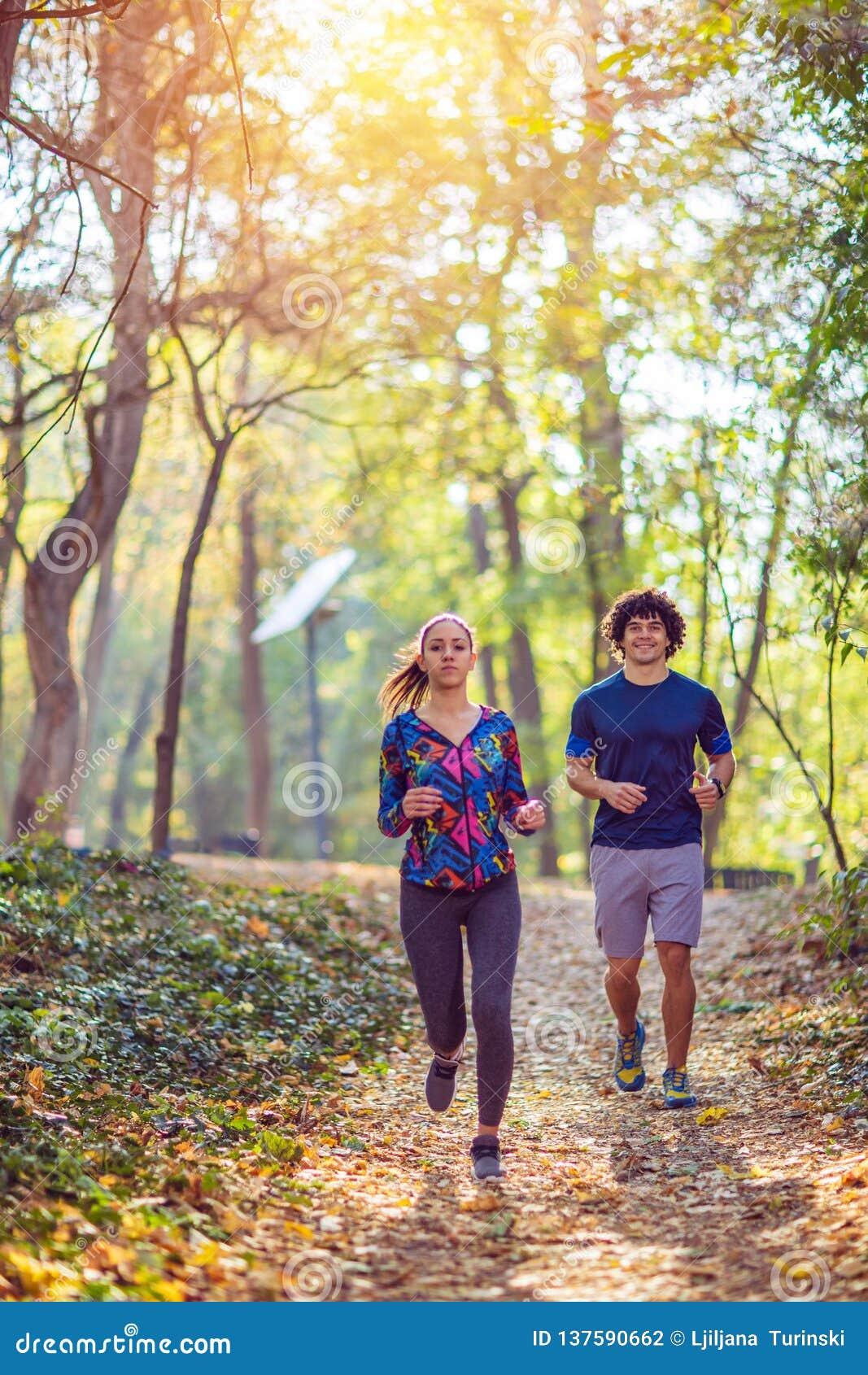 Cardio- exercício - par que aprecia em um estilo de vida saudável ao movimentar-se ao longo de uma floresta