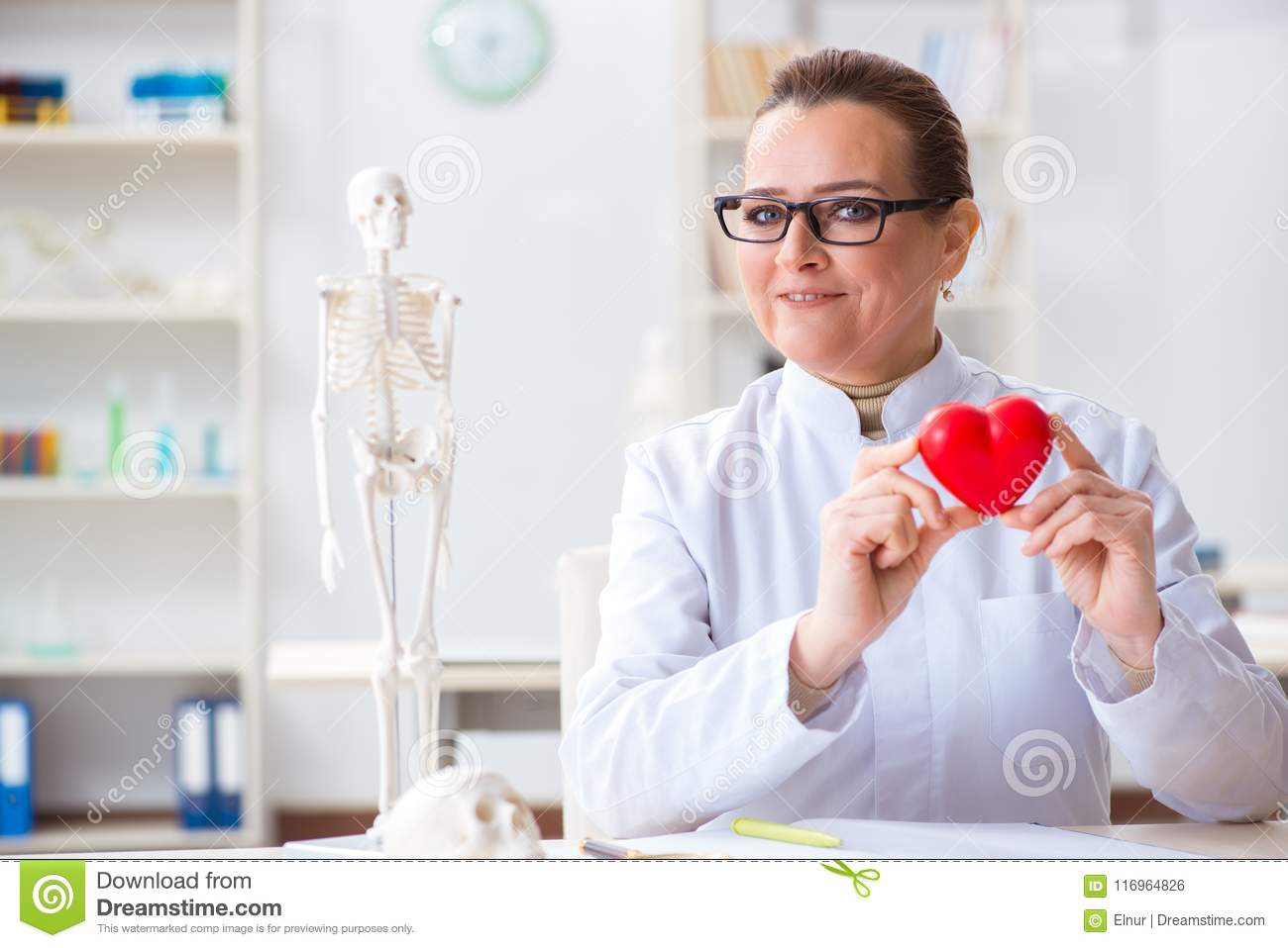 The cardiologist with red heart in medical concept