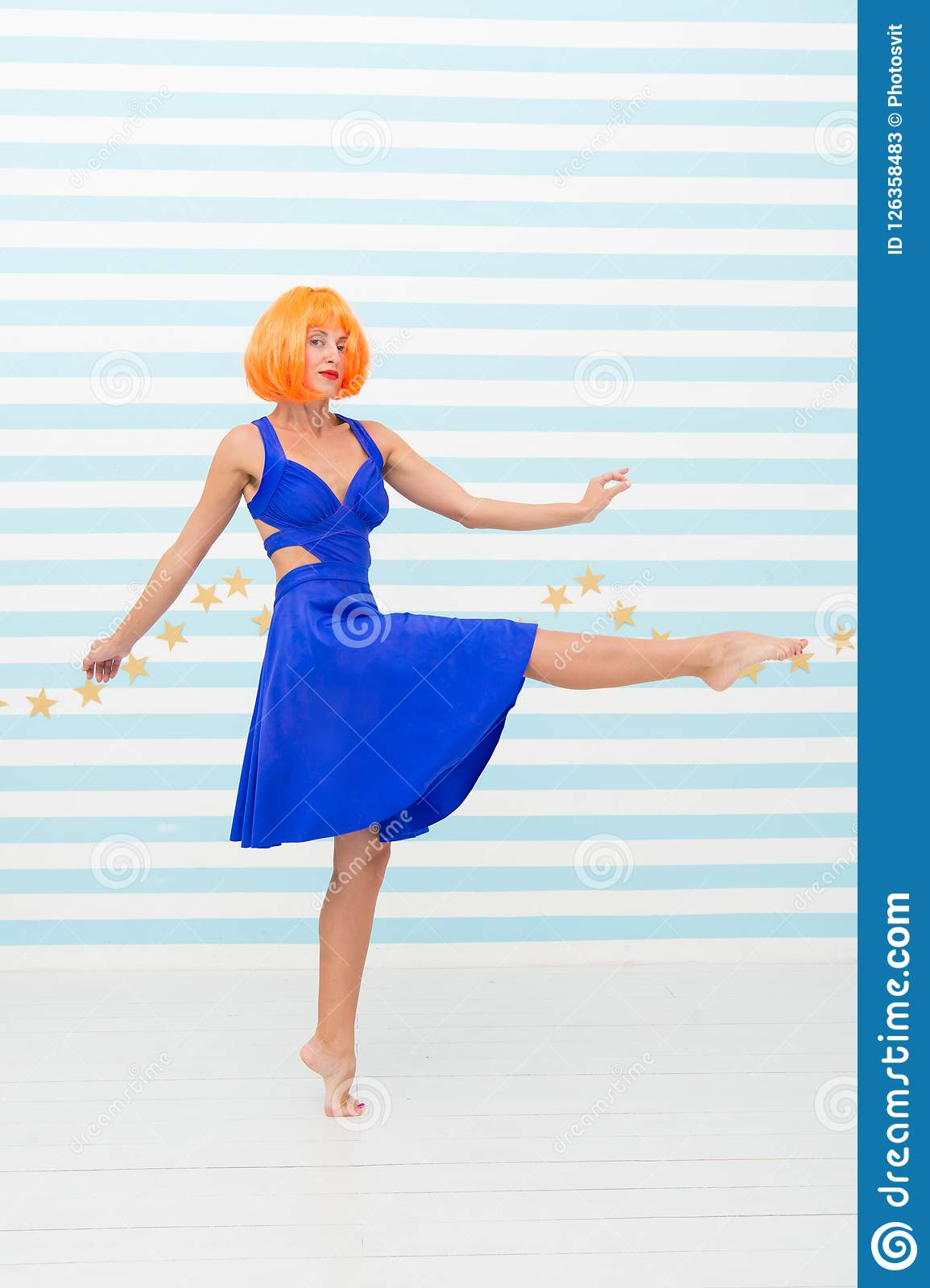Carefree girl with crazy look makes step. so much fun. crazy girl with orange hair dancing barefoot. totally carefree