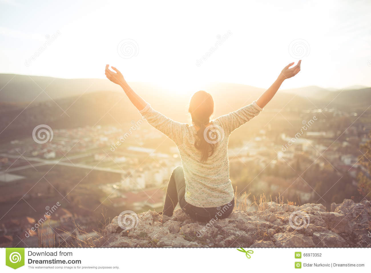 carefree-happy-woman-sitting-top-mountain-edge-cliff-enjoying-sun-her-face-raising-hands-sunlight-rays-enjoying-nature-66973352.jpg