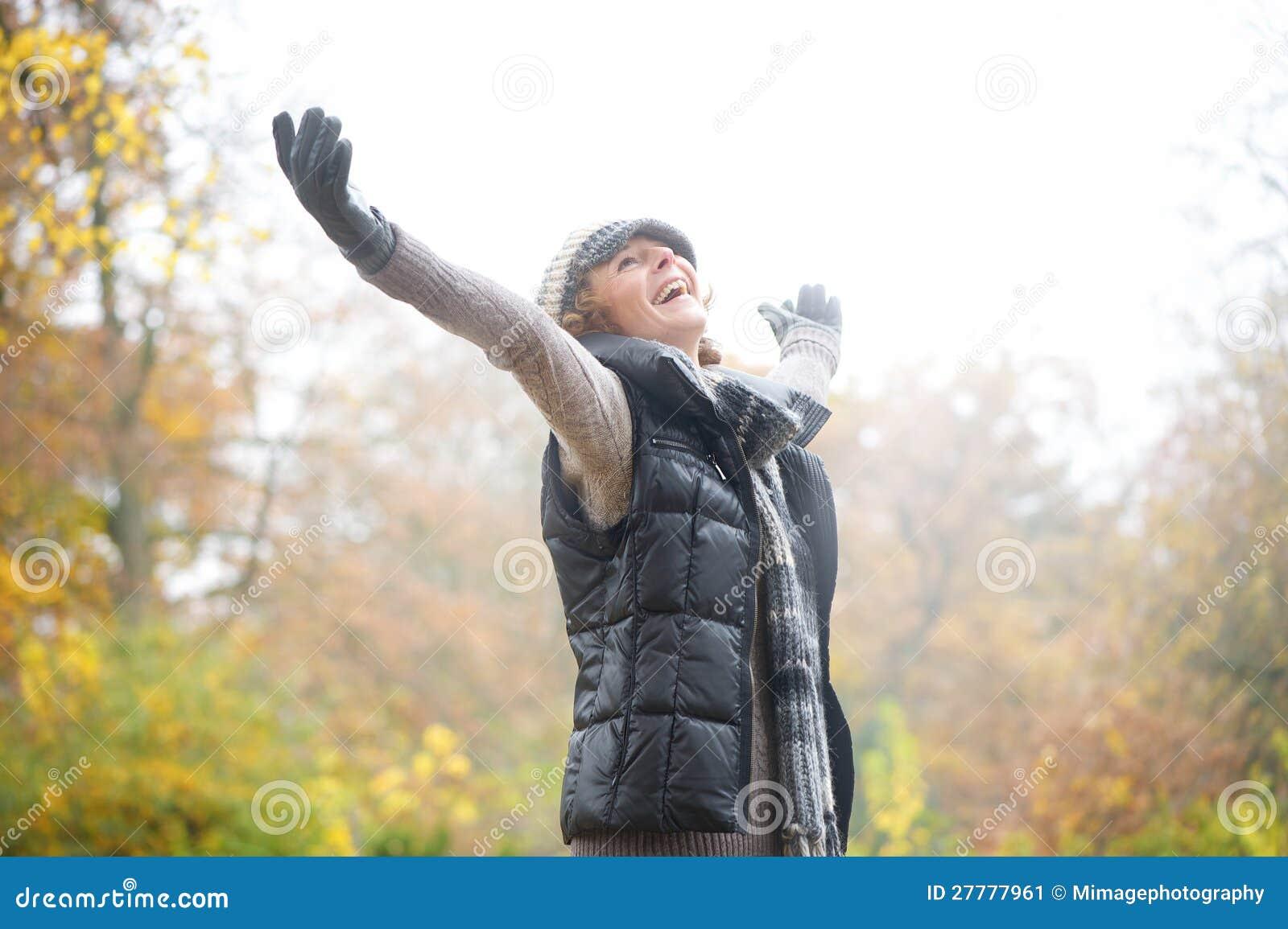 Carefree kvinna med Outstreched armar i höst